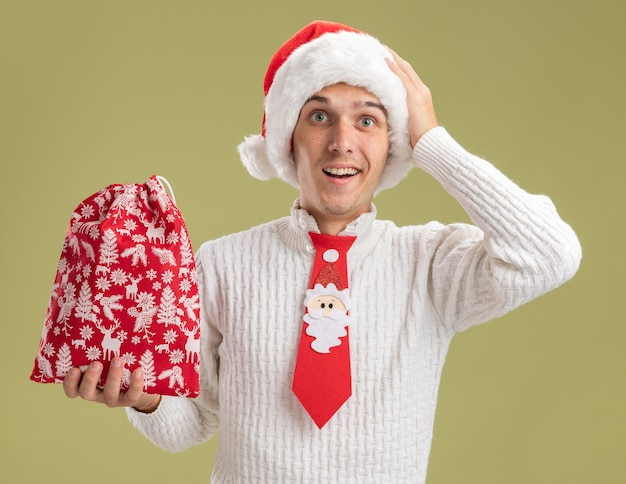 クリスマスの帽子とサンタクロースのネクタイを身に着けている感動の若いハンサムな男は、オリーブグリーンの背景で隔離のカメラを見て頭に手を置いてクリスマス袋を保持しています
