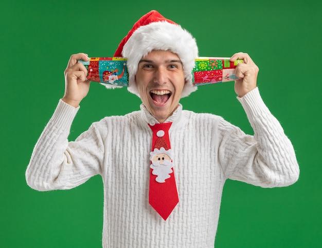 녹색 배경에 고립 된 카메라를보고 귀 옆에 플라스틱 크리스마스 컵을 들고 크리스마스 모자와 산타 클로스 넥타이를 입고 감동 젊은 잘 생긴 남자