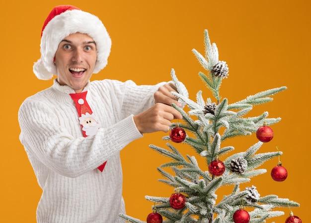 Впечатленный молодой красивый парень в новогодней шапке и галстуке санта-клауса, стоящий возле елки, украшающий ее украшением елочного шара, смотрящий в камеру, изолированную на оранжевом фоне