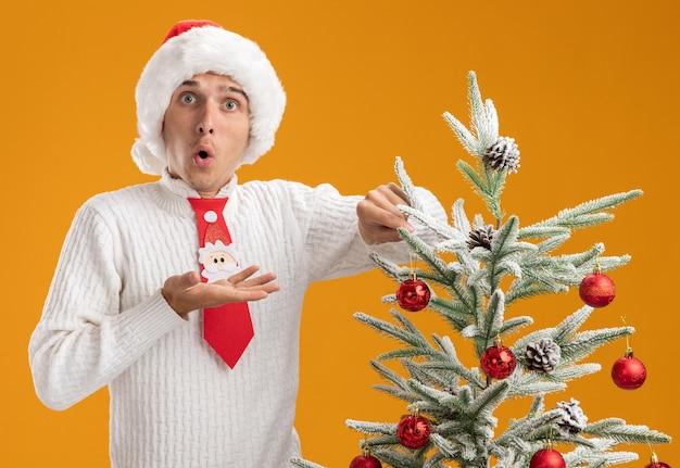 Впечатленный молодой красивый парень в новогодней шапке и галстуке санта-клауса, стоящий возле елки, украшающий ее украшением елочного шара, глядя, показывая пустую руку, изолированную на оранжевой стене