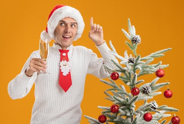 クリスマスの帽子とサンタクロースのネクタイを身に着けている感動の若いハンサムな男は、オレンジ色の背景に分離された側を上向きに見ているシャンパンのガラスを保持している装飾されたクリスマスツリーの近くに立っています