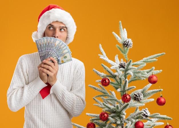 오렌지 벽에 고립 된 뒤에서 측면을보고 돈을 들고 장식 된 크리스마스 트리 근처에 서 크리스마스 모자와 산타 클로스 넥타이를 착용하는 감동 된 젊은 잘 생긴 남자