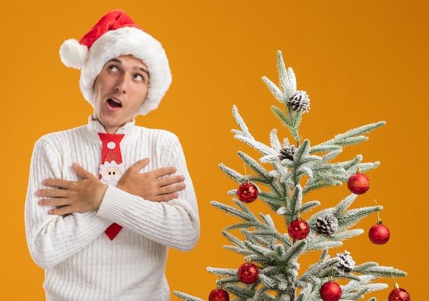 Впечатленный молодой красивый парень в новогодней шапке и галстуке санта-клауса стоит возле украшенной елки, скрестив руки на груди, глядя в сторону, изолированную на оранжевой стене