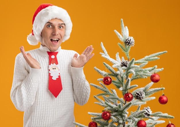 오렌지 배경에 고립 된 빈 손을 보여주는 카메라를보고 장식 된 크리스마스 트리 근처에 서 크리스마스 모자와 산타 클로스 넥타이를 입고 감동 젊은 잘 생긴 남자