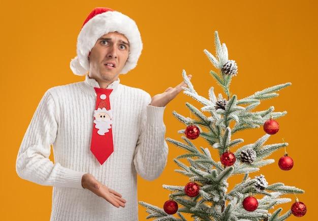 오렌지 배경에 고립 된 카메라를보고 손으로 그것을 가리키는 장식 된 크리스마스 트리 근처에 서 크리스마스 모자와 산타 클로스 넥타이를 입고 감동 젊은 잘 생긴 남자