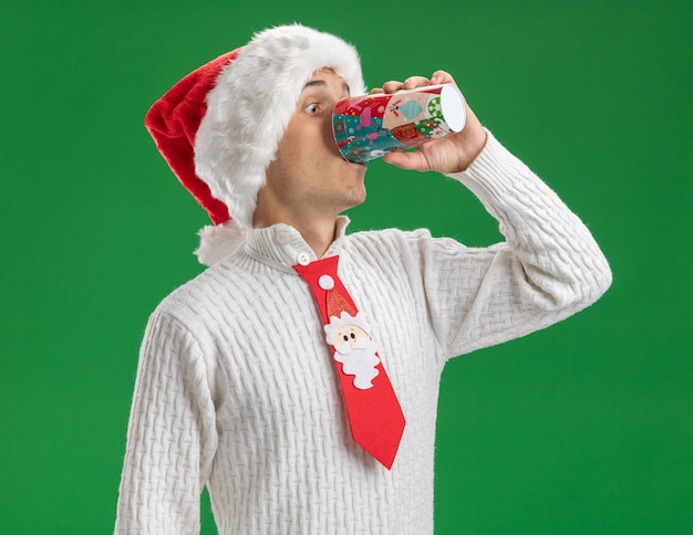 Impressed young handsome guy wearing christmas hat and santa claus tie drinking coffee from plastic christmas cup isolated on green wall