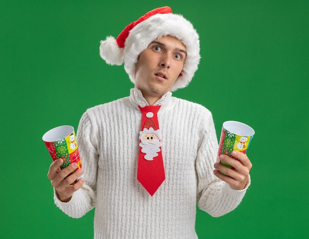 Impressed young handsome guy wearing christmas hat and santa claus tie holding plastic christmas cups looking at camera isolated on green background