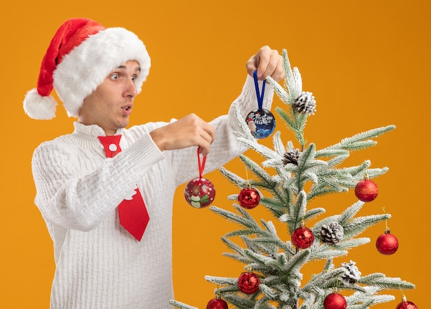 Impressed young handsome guy wearing christmas hat and santa claus tie standing near christmas tree decorating it with christmas ball ornaments looking at tree isolated on orange background