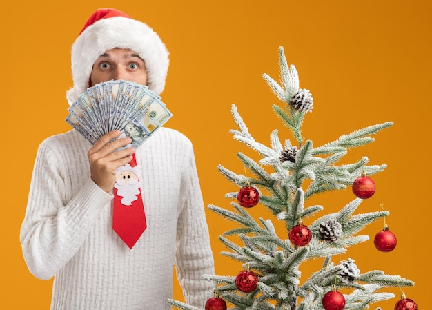 Impressed young handsome guy wearing christmas hat and santa claus tie standing near decorated christmas tree holding money looking at camera from behind it isolated on orange background