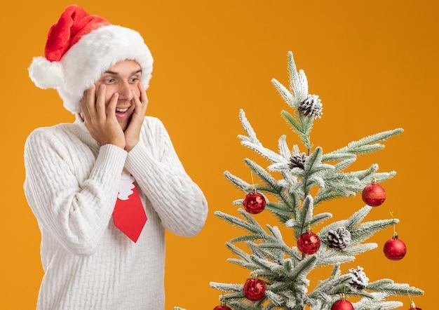 Impressionato giovane bel ragazzo che indossa cappello di natale e cravatta di babbo natale in piedi vicino all'albero di natale decorato tenendo le mani sul viso guardando in basso isolato sul muro arancione