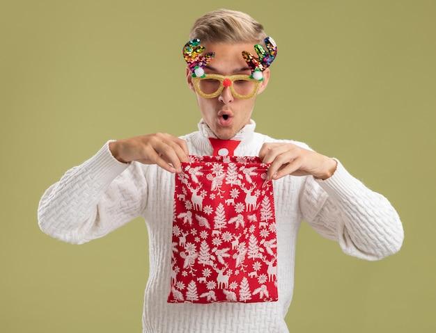 クリスマスノベルティメガネとサンタクロースのネクタイを身に着けている感動の若いハンサムな男は、オリーブグリーンの壁に隔離されたその中を見てオープニングクリスマス袋を保持しています