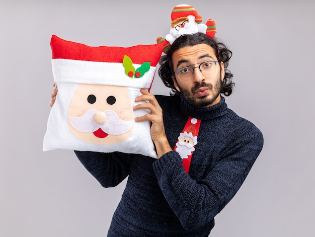 Impressed young handsome guy wearing christmas tie with hair hoop holding christmas pillow around face isolated on white background
