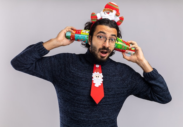 Impressed young handsome guy wearing christmas tie with hair hoop putting christmas cup on ears isolated on white background