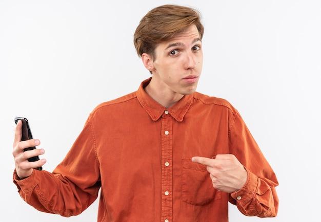 Impressionato giovane bel ragazzo che indossa una camicia rossa che tiene e indica il telefono
