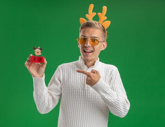 Впечатленный молодой красивый парень в головной повязке из оленьих рогов в очках, держащий и указывающий на елочную игрушку с датой, глядя в камеру, изолированную на зеленом фоне