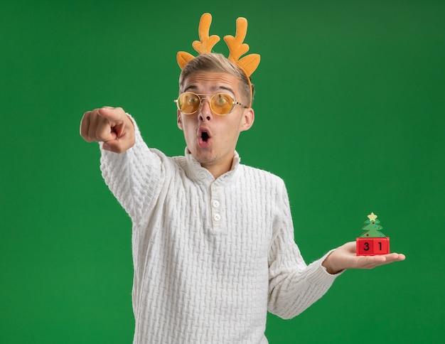 Впечатленный молодой красивый парень в головной повязке с оленьими рогами в очках, держащий елочную игрушку с датой, глядя и указывая на сторону, изолированную на зеленом фоне