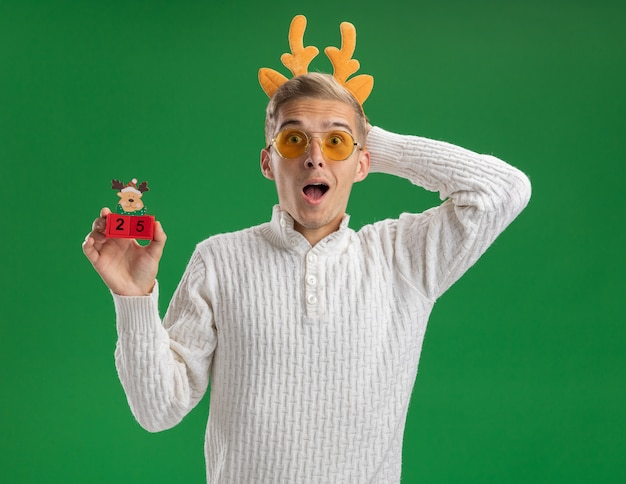 Impressed young handsome guy wearing reindeer antlers headband with glasses holding christmas tree toy with date looking at camera keeping hand behind head isolated on green background