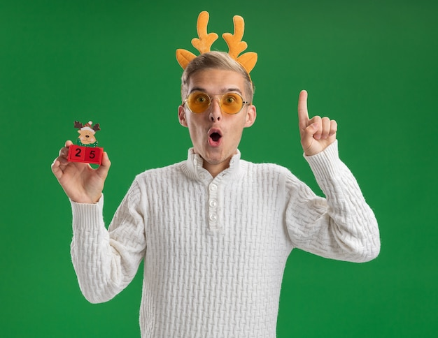 Impressed young handsome guy wearing reindeer antlers headband with glasses holding christmas tree toy with date looking at camera pointing up isolated on green background