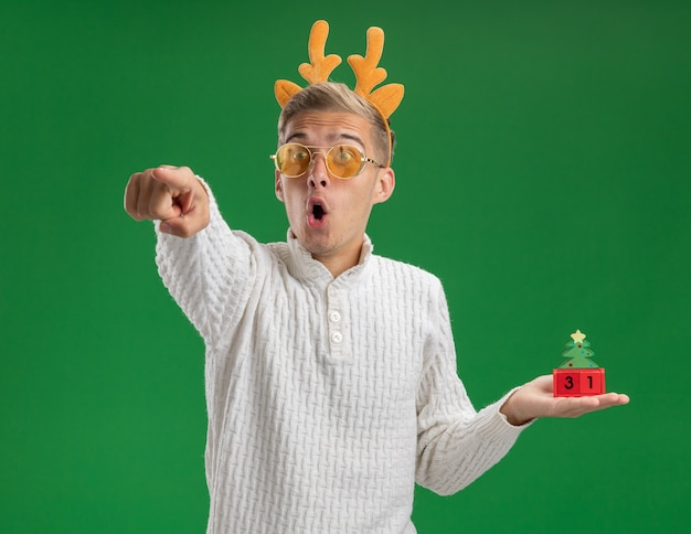 Impressed young handsome guy wearing reindeer antlers headband with glasses holding christmas tree toy with date looking and pointing at side isolated on green background