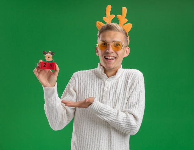 緑の背景に分離されたカメラを見て手でそれを指している日付とクリスマスツリーのおもちゃを保持しているメガネとトナカイの角のヘッドバンドを身に着けている感動の若いハンサムな男