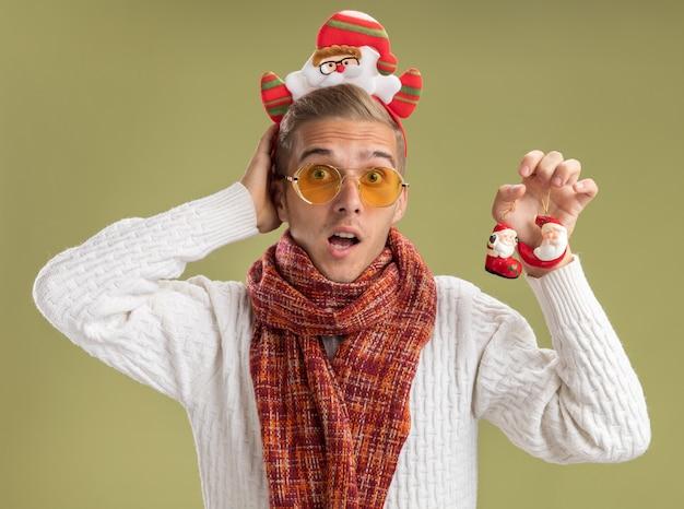 サンタクロースのヘッドバンドとサンタクロースのクリスマスの飾りを持っているスカーフを身に着けている感動の若いハンサムな男は、オリーブグリーンの背景で隔離の頭の後ろに手を保ちながらカメラを見て