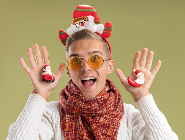 サンタクロースのヘッドバンドとスカーフを身に着けている印象的な若いハンサムな男は、オリーブグリーンの背景に分離されたカメラを見てサンタクロースのクリスマスの飾りを保持しているカメラを見て