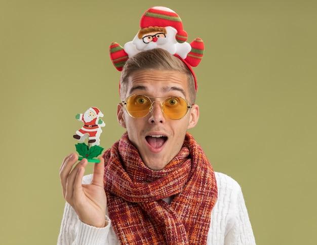 サンタクロースのヘッドバンドとスカーフを身に着けている印象的な若いハンサムな男は、オリーブグリーンの背景で隔離のサンタクロースのおもちゃを保持しているカメラを見て