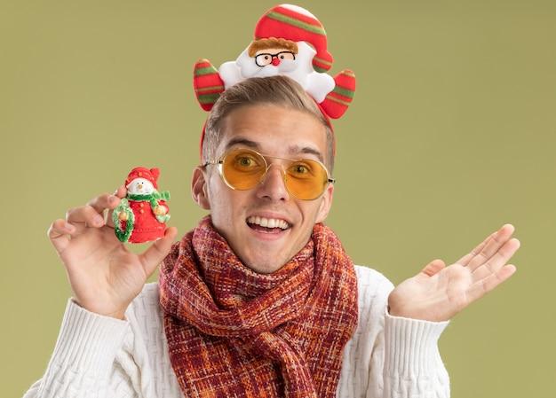 サンタクロースのヘッドバンドとスカーフを身に着けている印象的な若いハンサムな男は、オリーブグリーンの背景で隔離の空の手を示す雪だるまのクリスマス飾りを保持しているカメラを見て