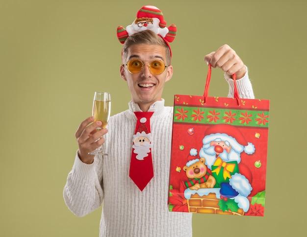 Впечатленный молодой красивый парень в повязке на голову санта-клауса и галстуке, смотрящий в камеру, держащую бокал шампанского и рождественский подарочный пакет, изолированный на оливково-зеленом фоне