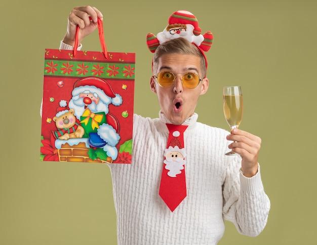 Впечатленный молодой красивый парень в повязке на голову санта-клауса и галстуке, смотрящий в камеру, держащий бокал шампанского и поднимающий рождественский подарочный пакет, изолированный на оливково-зеленом фоне