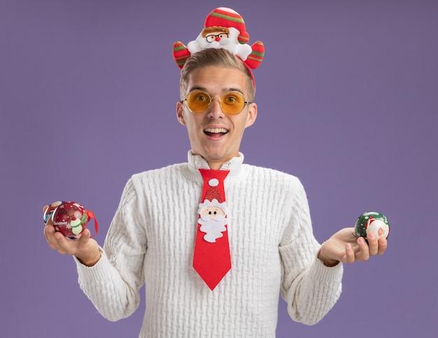 サンタクロースのヘッドバンドを身に着けて、紫色の背景に分離されたカメラを見てクリスマスボールの飾りを保持しているメガネとネクタイに感銘を受けた若いハンサムな男