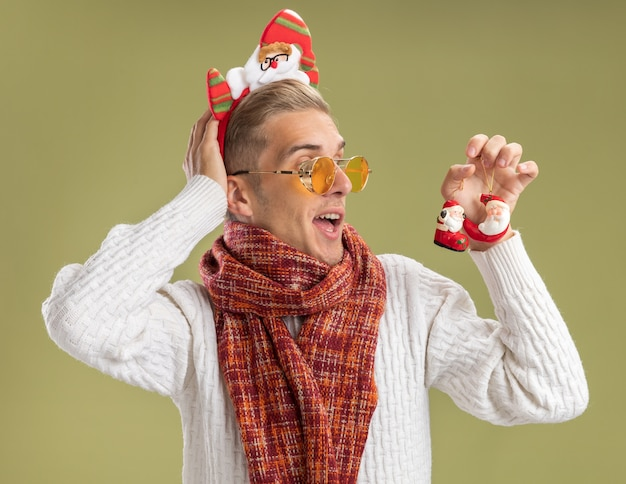Impressed young handsome guy wearing santa claus headband and scarf holding and looking at santa claus christmas ornaments putting hand behind head isolated on olive green background