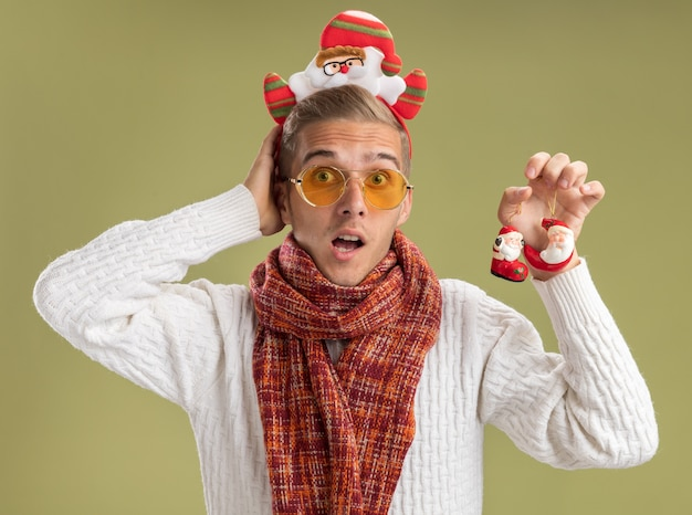 Impressed young handsome guy wearing santa claus headband and scarf holding santa claus christmas ornaments looking at camera keeping hand behind head isolated on olive green background