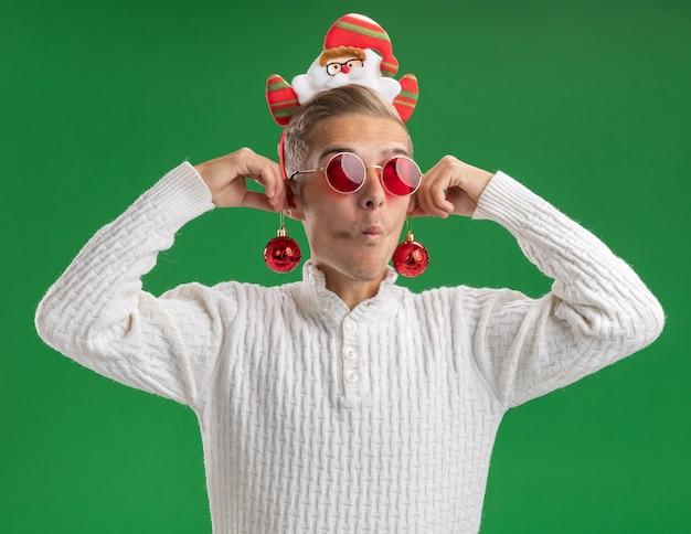 Impressionato giovane bel ragazzo che indossa la fascia di babbo natale con gli occhiali che appendono le bagattelle di natale sulle orecchie guardando il lato con le labbra increspate isolato su priorità bassa verde