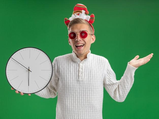 緑の背景に分離された空の手を示すカメラを見て時計を保持しているメガネとサンタクロースのヘッドバンドを身に着けている感動の若いハンサムな男