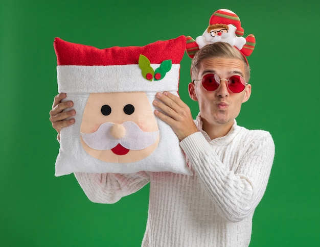 Impressed young handsome guy wearing santa claus headband with glasses holding santa claus pillow looking at camera doing kiss gesture isolated on green background