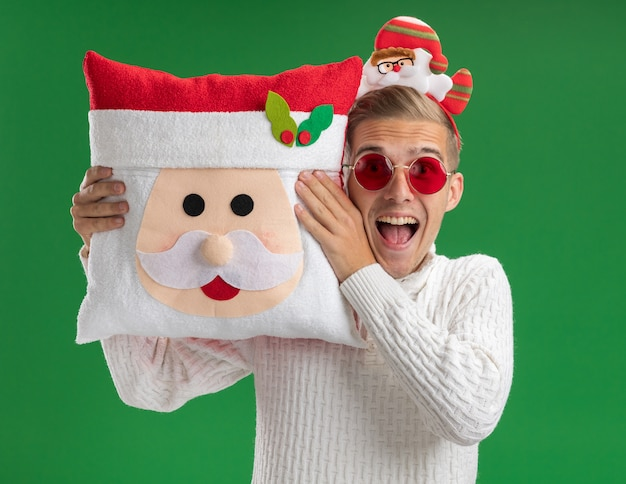 Impressed young handsome guy wearing santa claus headband with glasses holding santa claus pillow near head looking at camera isolated on green background