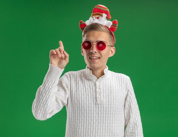 Впечатленный молодой красивый парень в головной повязке санта-клауса в очках, смотрящий в сторону и указывающий вверх, изолированный на зеленой стене