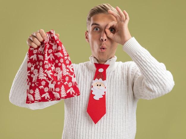 Впечатленный молодой красивый парень в галстуке санта-клауса, держащий рождественский мешок, смотрящий в камеру, делает жест взгляда изолирован на оливково-зеленом фоне