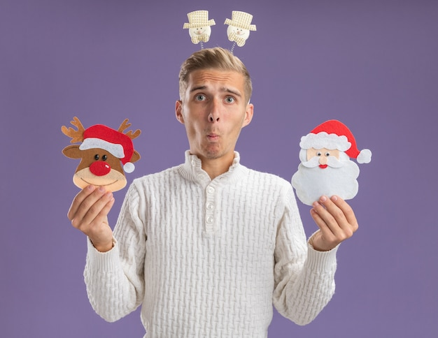 クリスマスのトナカイとサンタクロースの紙の装飾品を保持している雪だるまのヘッドバンドを身に着けている感動の若いハンサムな男は、紫色の背景に分離された口すぼめ呼吸でカメラを見て