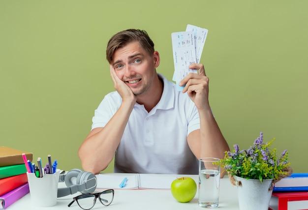 올리브 그린에 고립 된 티켓을 들고 학교 도구로 책상에 앉아 감동 젊은 잘 생긴 남자 학생