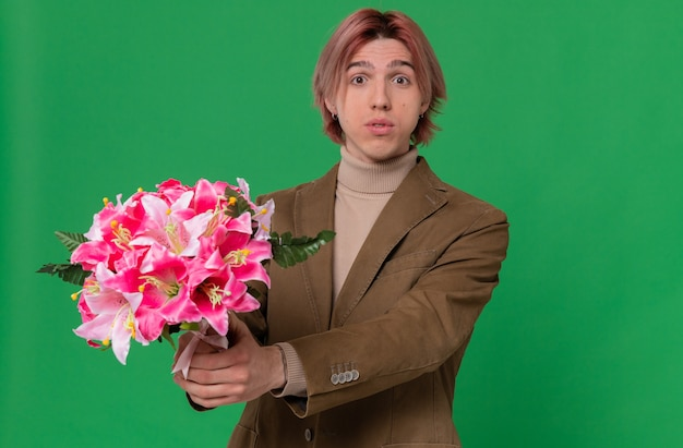 Impressed young handsome man holding out bouquet of flowers looking