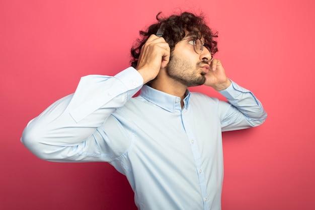 ピンクの壁に隔離された側を見てキスジェスチャーをしている眼鏡とヘッドフォンをつかんでいる印象的な若いハンサムな男