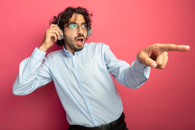 ピンクの壁に隔離された側を見て、指しているヘッドフォンをつかんで眼鏡とヘッドフォンを身に着けている印象的な若いハンサムな男