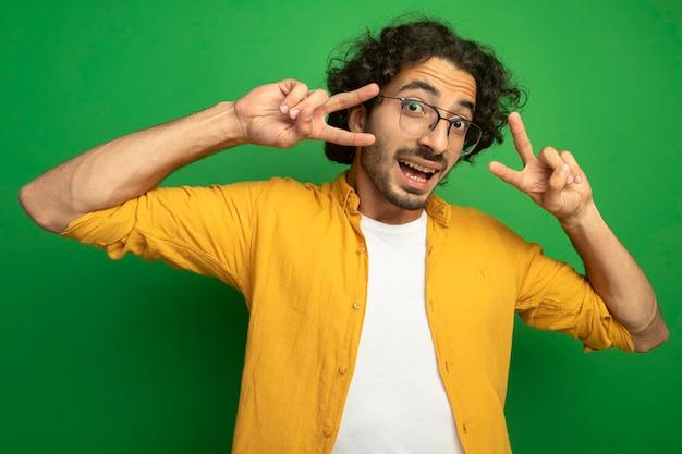Впечатленный молодой красавец в очках делает знак мира, глядя на фронт, изолированный на зеленой стене