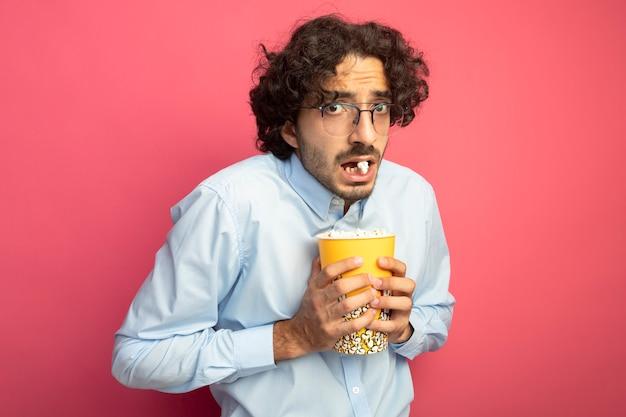 ピンクの壁に分離された口の中にポップコーンの部分で正面を見てポップコーンのバケツを保持している眼鏡をかけて感動した若いハンサムな男