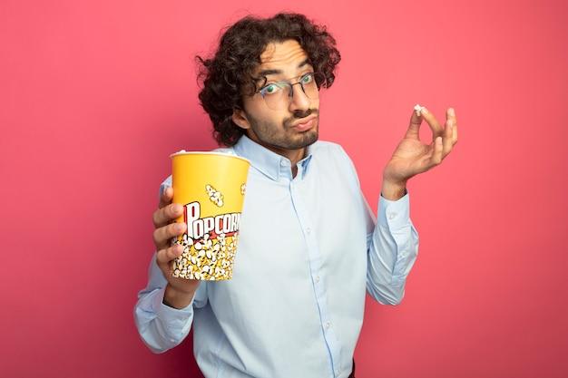 Impressionato giovane uomo bello con gli occhiali che tiene secchio di popcorn e pezzo di popcorn guardando davanti isolato sul muro rosa
