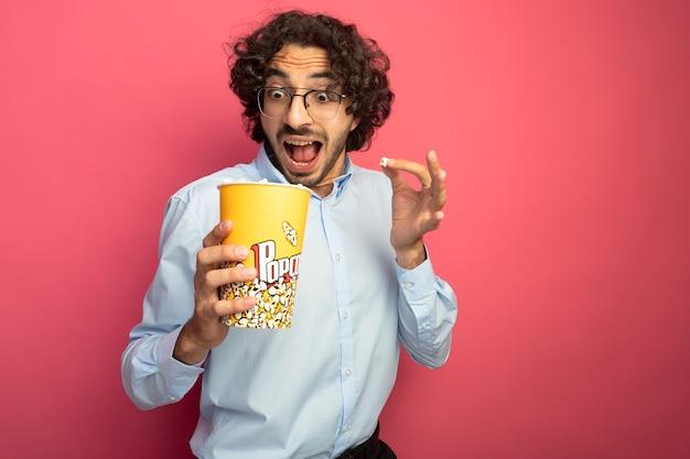 Impressionato giovane uomo bello con gli occhiali tenendo e guardando all'interno del secchio di popcorn e tenendo un pezzo di popcorn isolato sul muro rosa
