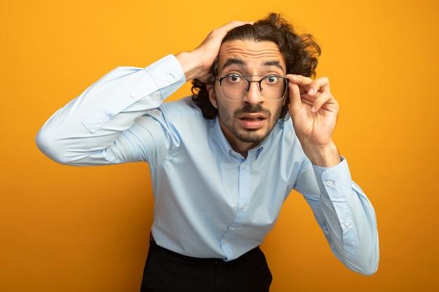 Впечатленный молодой красавец в очках, держащий руку на голове, хватаясь за очки, смотрящий вперед, изолированный на оранжевой стене