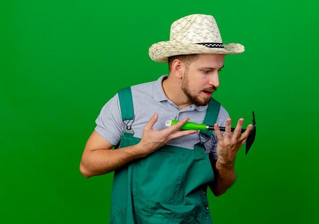 Впечатленный молодой красивый славянский садовник в форме и шляпе держит и смотрит на грабли